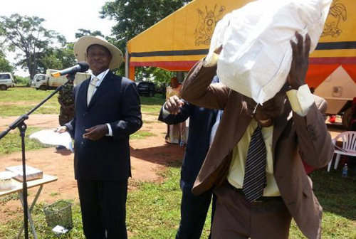 CASH IN A SACK: President Museveni (left) looks on as the chairperson of Busoga Youth Forum receives a sack stacked with USh250 million (~$100,000) as donation to the Youth Group. This donation was the latest in a long list of public handouts personally given out by Mr Museveni. PHOTO: chimpreports.com